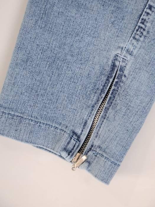 Dżinsowe spodnie z ozdobnymi zamkami 29744
